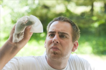 A young man cleaning the window with a paper towel and window cleaner. Stock Photo