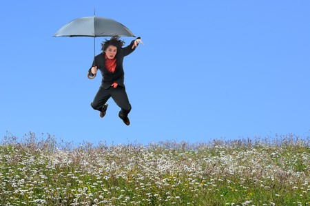 Young businessman jumping over a grass field with blank blue sky copyspace. photo