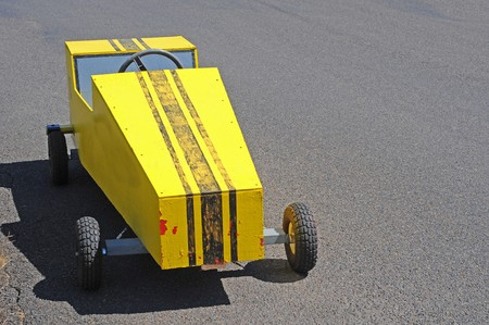 A yellow soapbox derby race cart on a racing track. photo