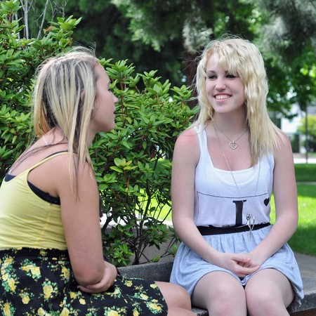 Two teenage girl friends sitting in front of a high school building on a bench talking and socializing with each other with their bags beside them. photo