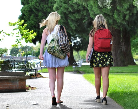 Two young attractive girls wearing skirts walk in front of a public school with their back packs on them. Stock Photo