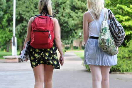 szoknya: Two young attractive girls wearing skirts walking in front of a public school with their back packs on.