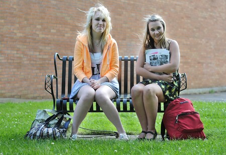 Two teenage girl friends sitting in front of a high school building on a bench talking and studying with each other with their bags beside them. photo