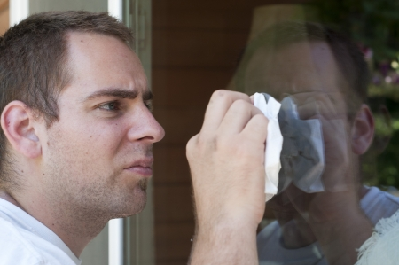 A young man cleaning the window on his house with a paper towel. photo