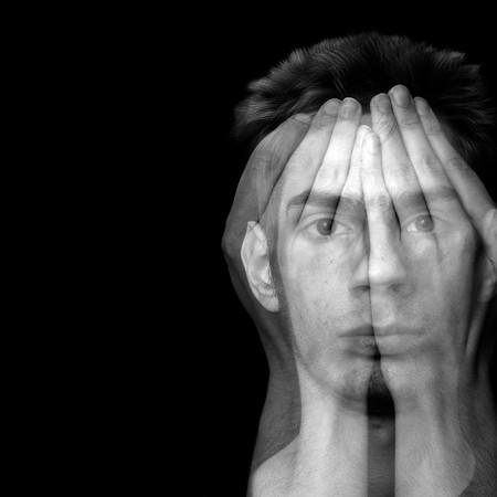 esquizofrenia: Macho joven que cubre su rostro con sus manos sobre un fondo negro con copyspace.  Foto de archivo