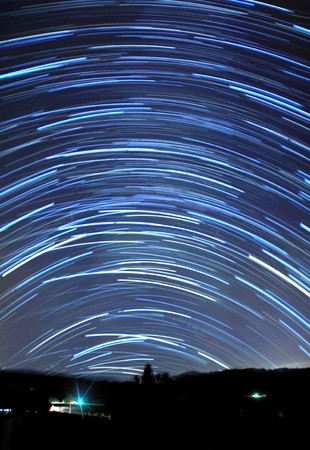Long blue star trails in the sky above a mountain. photo