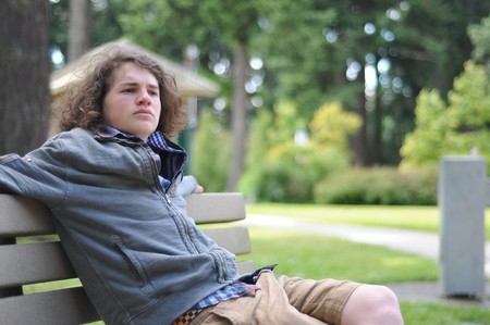 Young white Caucasian teenager sits on a bench in a public park, relaxing while he thinks things over.