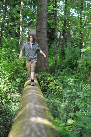 A young adult walking across a fallen tree going across a river in the woods photo