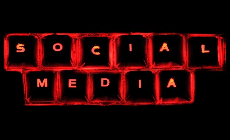 The word social media on a glowing computer keyboard isolated on black. photo