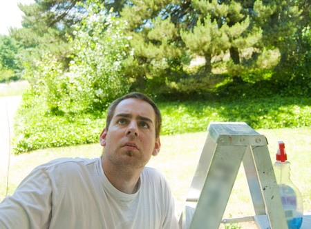 A young man looking up at the window standing on a ladder with window cleaner. photo