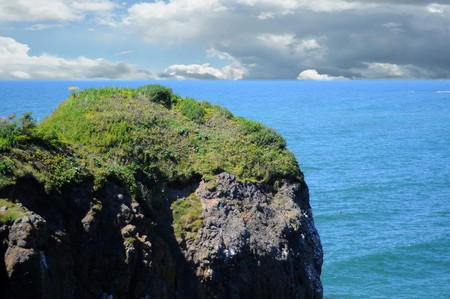 dropoff: Large rock cliff with grass growing on the top of it with the ocean right underneath Stock Photo