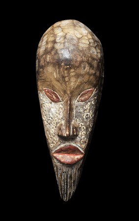 african tribe: Wooden carved voodoo tiki mask isolated on a pitch black background. Stock Photo