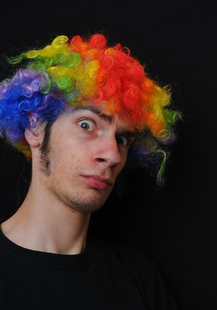 A silly crazy man wearing a clown wig with rainbow colors staring at the camera with a serious look. photo