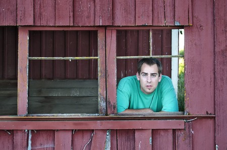 A young adult white Caucasian farmer man looks out the broken window inside of his old barn. photo