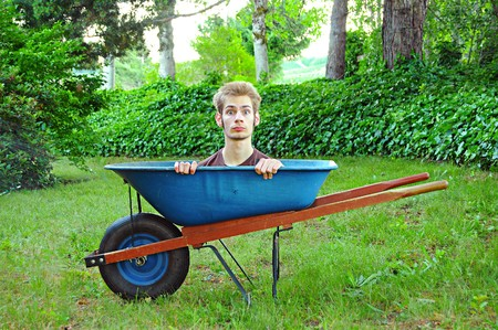 A young teenager inside of a wheel barrow, scared to do his chores. photo