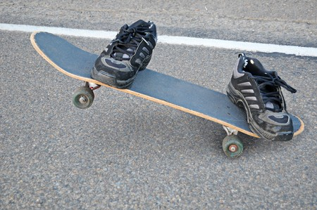 An invisible skateboarder riding a skateboard, only his shoes can be seen, where the rest of his body is transparent. photo