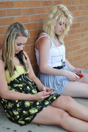 Two teenage girls sitting next to a brick wall texting on their mobile cellphones. photo