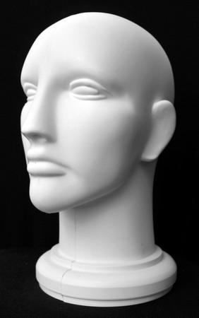 Front view of a mannequin dummy head isolated on a black background. photo