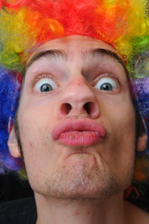 A silly crazy man wearing a clown wig with rainbow colors pucking his lips out for a kiss photo