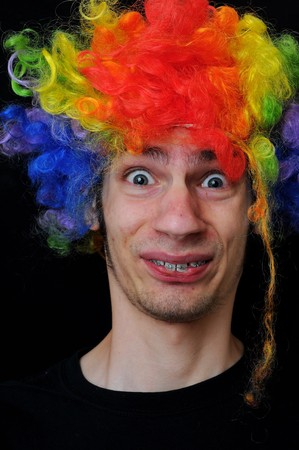 A silly crazy man wearing a clown wig with rainbow colors photo