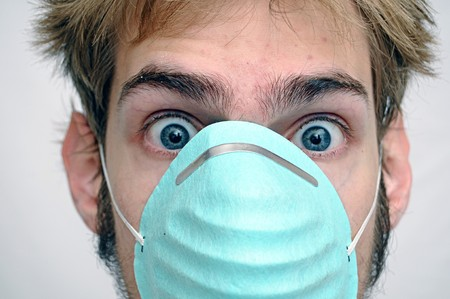 respiratory apparatus: Young man wearing a teal dustdoctor mask with wide open eyes