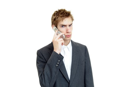 Young businessman talks on cell phone with a sort of confused, sad, impatient look on his face. Stock Photo