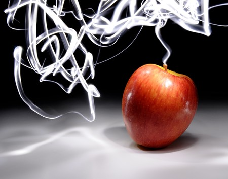 streaks of light: An apple sitting on a white surface with light painting streaks above and around the apple. Stock Photo