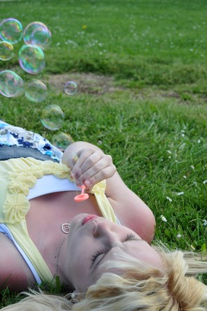 Young white Caucasian teenage girl laying in grass blowing bubbles. Stock Photo - 7549912