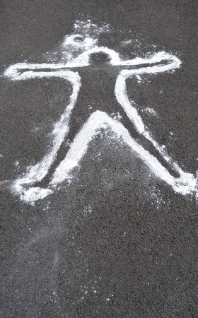 crime: A white chalk outline of a dead body on asphalt cement.