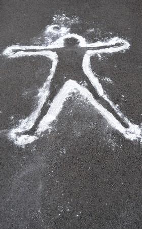 crime: A white chalk outline of a dead body on asphalt cement.