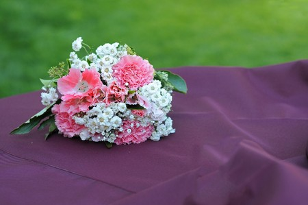 A bouquet of flowers resting on a table with grass copyspace above.
