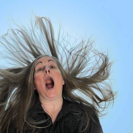 blown away: A woman screaming in front of a blue background with her hair blasting behind her. Stock Photo