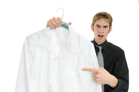 messy clothes: Unsatisfied customer holds up a dry cleaned suit. Missed a spot! Stock Photo