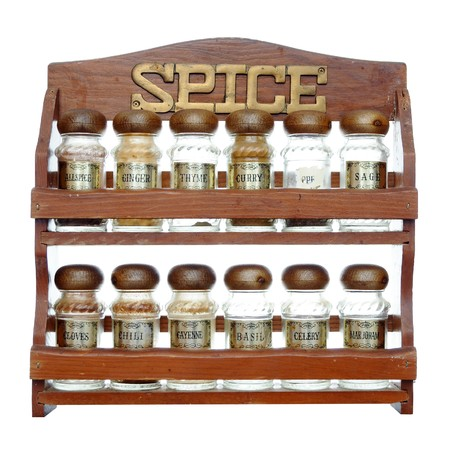 An old wooden spice rack isolated on white background. Most of the bottles are empty.