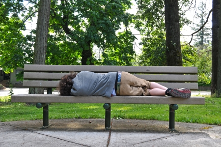 A homeless person takes a nap on a bench in a public park. Stockfoto