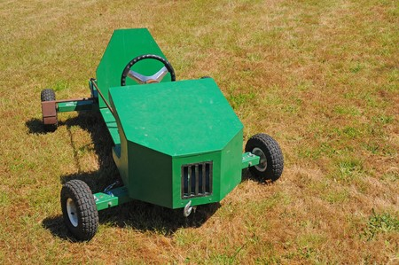 unpainted: A green soapbox racing car displayed on the grass.