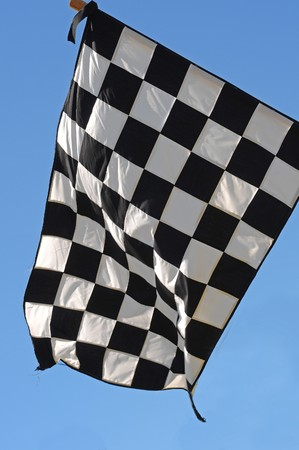 A checkered racing flag with a blue sky in the background.