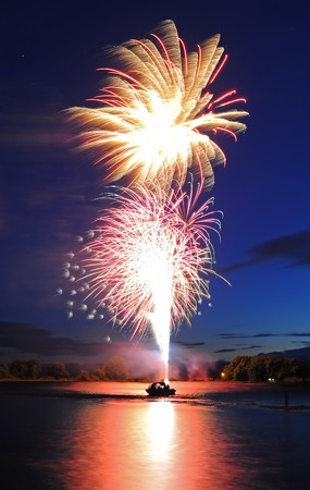 firework display: Fireworks launching from a boat floating on the river up into the sky. Stock Photo