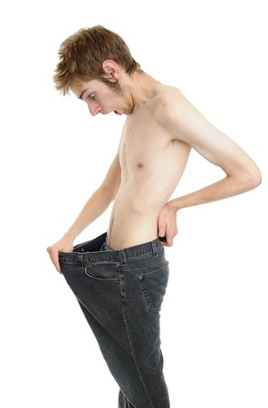 thin: A young man looking down at his old pants when he was fat. Looks like he lost some weight and is now thin! Isolated on white.