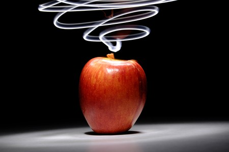 electrifying: An apple sitting on a white surface with light painting streaks above and around the apple. Stock Photo