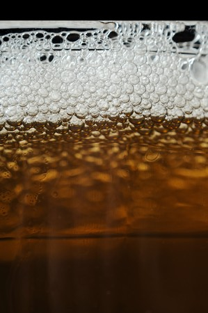 A closeup of dark beer in a cup with bubble suds at the top Stock Photo - 7618077