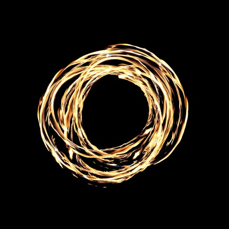 A hot circle of firey flames on a black background created by a fire dancer. Banque d'images