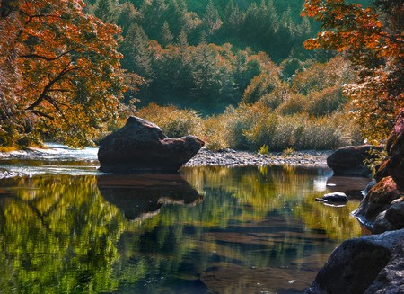 autum: A rocky river with waters so calm it is almost like a lake. This photograph was taken in Oregon. Stock Photo