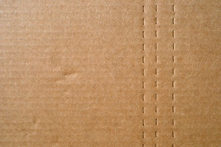 Flat brown cardboard  background texture with perforated lines that will help the box fold. photo