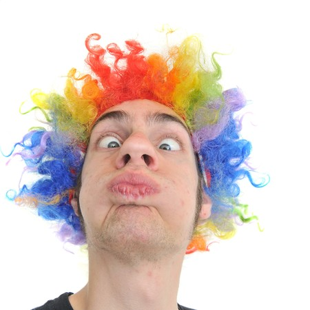 A white Caucasian young adult wearing a silly clown wig with rainbow colorful hair. photo