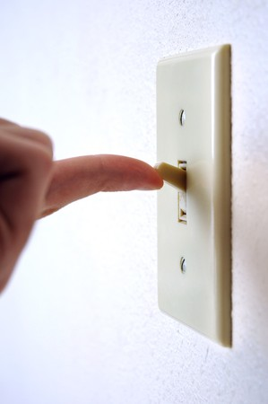A single light switch on a white wall at an angle with a finger flipping it up, to turn it on. 版權商用圖片