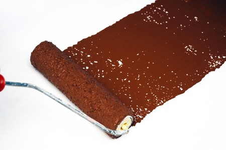 Wet brown paint being painting on a whire surface with a roller. photo