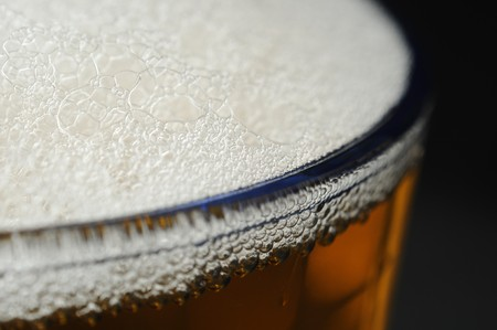 A closeup of dark beer in a cup with bubble suds at the top Stock Photo - 7618518