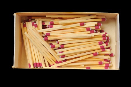 pyromania: A bunch of wooden matches in a box isolated on a black background