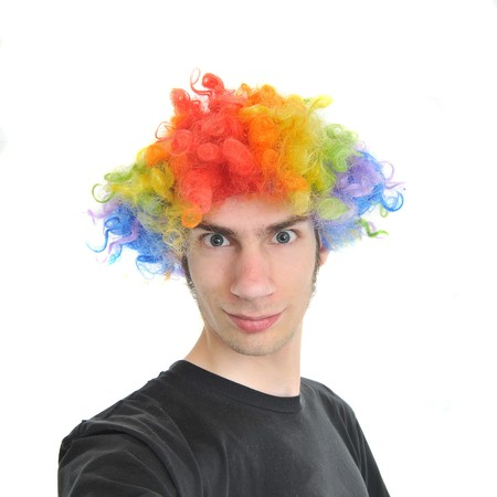 A white Caucasian young adult wearing a silly clown wig with rainbow colorful hair. Фото со стока